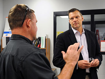 Richard Fairchild (left), auto collision repair instructor at Salina Area Technical College, talks with Kansas Secretary of State Kris Kobach during a tour of the school Tuesday morning. [TOM DORSEY / SALINA JOURNAL]